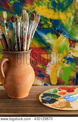 Paint brush in clay jug and art painting abstract background texture. Paintbrush for oil painting as artistic paint still life. Abstract art concept