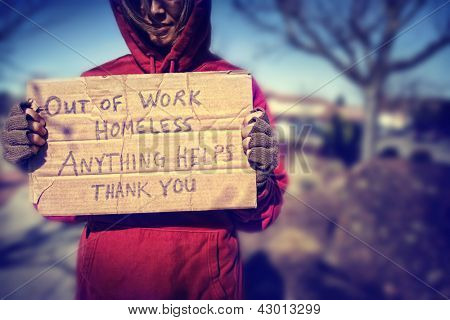 a homeless person with a sign poster