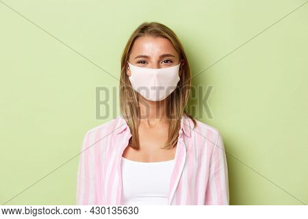 Concept Of Quarantine, Coronavirus And Lifestyle. Close-up Of Blond Cute Girl In Face Mask, Smiling