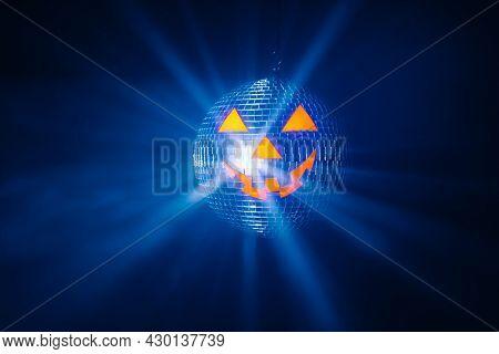 Halloween party pumpkin disco ball, blue shiny rays background