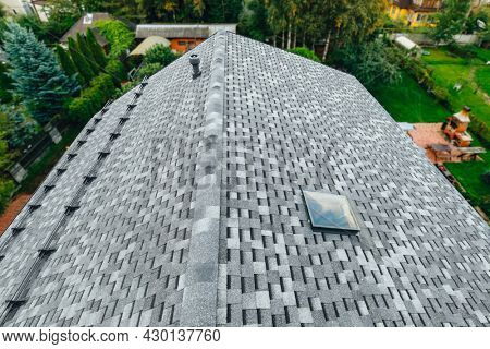 roof of new house with shingles roof-tiles, ventilation window and snow retention system