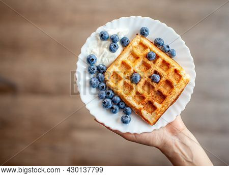 A Woman Holds In Her Hand A Plate On Which Fresh Waffles With Berries Are Ready. Homemade Waffles Wi