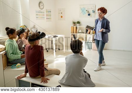 Teacher with tablet giving instructions to group of schoolkids before presentation