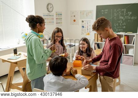Cute multiracial schoolkids having snack by desk during lunch break