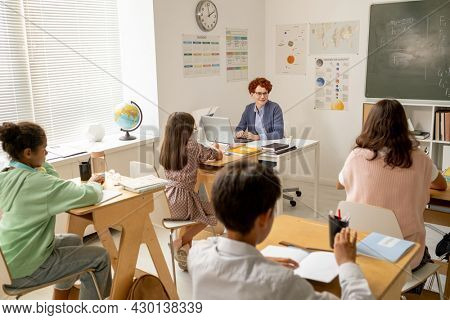 Young teacher sitting by workplace in front of schoolkids at lesson of physics