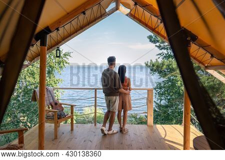 rear view of affectionate couple enjoying summer vacation in glamping house