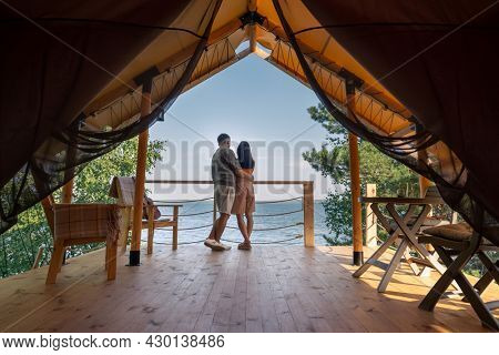 Rear view of amorous couple standing close to each other and looking at blue ocean while enjoying summer vacation