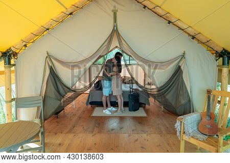 Young amorous couple standing in embrace by double bed inside glamping house