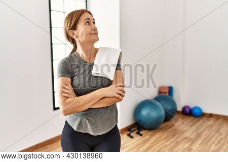 Middle age woman wearing sporty look training at the gym room looking to the side with arms crossed convinced and confident