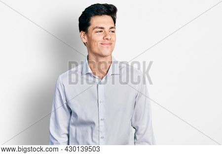 Young hispanic business man wearing business clothes smiling looking to the side and staring away thinking.
