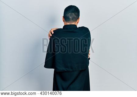Handsome hispanic man with beard wearing catholic priest robe hugging oneself happy and positive from backwards. self love and self care