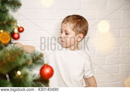 Funny Child Decorating The Christmas Tree With Balls. Christmas Eve Concept. Decorating Christmas Tr