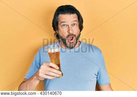 Middle age caucasian man drinking a pint of beer scared and amazed with open mouth for surprise, disbelief face