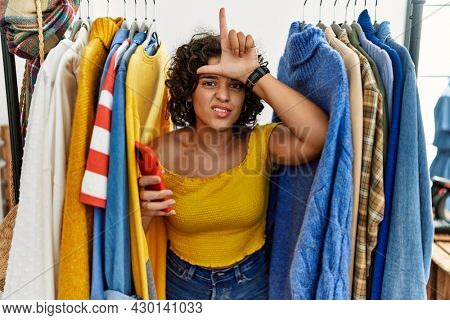 Young hispanic woman searching clothes on clothing rack using smartphone making fun of people with fingers on forehead doing loser gesture mocking and insulting.