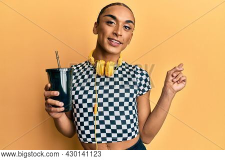 Hispanic man wearing make up and long hair wearing headphones and drinking take away soda smiling happy pointing with hand and finger to the side
