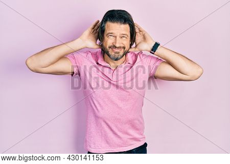 Middle age caucasian man wearing casual white t shirt trying to hear both hands on ear gesture, curious for gossip. hearing problem, deaf