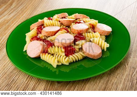 Green Glass Plate With Boiled Pasta Fusilli, Fried Sausages And Tomato Sauce On Wooden Table