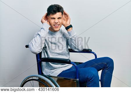 Young hispanic man sitting on wheelchair trying to hear both hands on ear gesture, curious for gossip. hearing problem, deaf