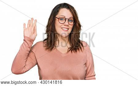 Young plus size woman wearing casual clothes and glasses waiving saying hello happy and smiling, friendly welcome gesture