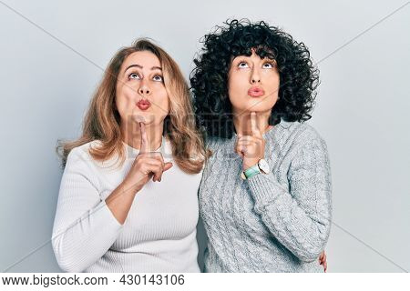 Middle east mother and daughter wearing casual clothes thinking concentrated about doubt with finger on chin and looking up wondering