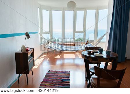 Vintage room with old fashioned armchair, retro radio turntable, table with food, telephone, standart lamp, doormat, chairs, hammock and sea view. Interior of 20th century, nostalgia