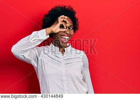 Young african american woman wearing casual clothes and glasses smiling happy doing ok sign with hand on eye looking through fingers