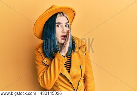 Young modern girl wearing yellow hat and leather jacket hand on mouth telling secret rumor, whispering malicious talk conversation