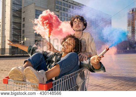 Contemporary teens with firecrackers having fun against urban environment