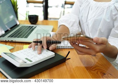 Businesswoman Calculating With Calculator, Holding Smartphone, Laptop On Desk