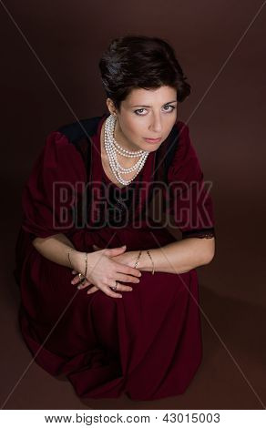 Young woman portrait with pearl on brown background poster