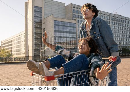 Happy girl with her arms outstretched enjoying time with her boyfriend while sitting in shopping cart