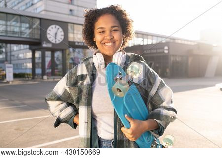 Young attractive skateboarder in casualwear looking at you with toothy smile