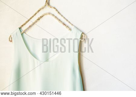 Light Blue Tank Top Hanging On A Hanger In A White Wall. Close Up And Copy Space.