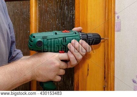 A Man Unscrews A Screw From A Door Frame. Dismantling The Wooden Door Trim. Uses A Screwdriver. Faci