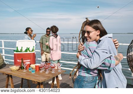 Happy smiling young woman in sunglasses hugging her friends she met at birthday party on pier