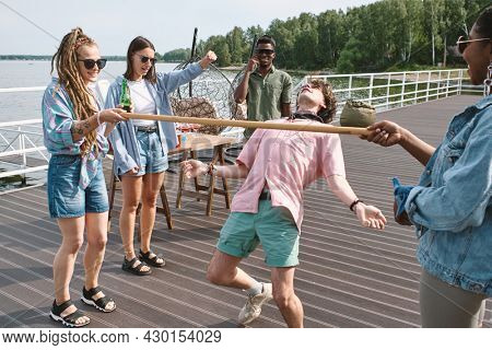 Group of young people gathered on wooden pier to have a party and play limbo game