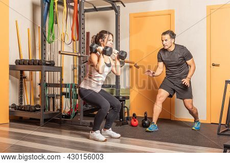 Athlete Woman Doing Squats With Dumbbells In Gym