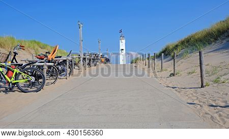 The lighthouse with the dutch flag in Noordwijk aan Zee in front of the entrance to the beach in the Netherlands