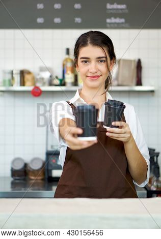 Young Caucasian Barista Dressed In Apron Hold Coffee Drink In Plastic Cup With Both Hands In Front O