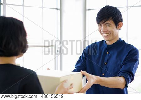 The Delivery Staff In A Black Uniform Handed The Box To The Young Customer. The Man Smiled Happily S