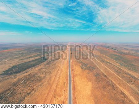 Amazing Panorama Of The Steppe And A Straight Line Of The Highway Through The Sandy Desert In The As