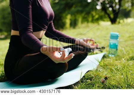Meditation And Yoga In Park Outdoors. Close-up Of Young Woman In Sportswear Meditates On Yoga Mat, S