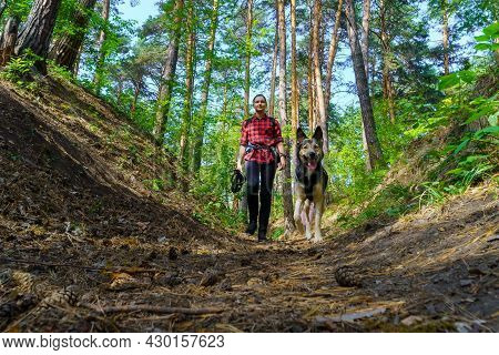 A Girl Walks Through The Summer Forest With A Dog. Summer Time. Walking, Tourism, Travel