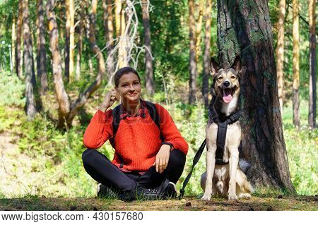 A Young Girl In A Red Jacket Is Sitting In The Forest With Her Dog During A Walk