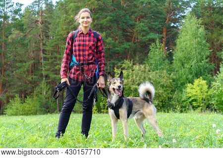 A Young Girl In A Red Shirt With Her Dog Stands Against The Background Of The Forest. Walking With A