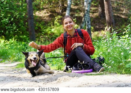 A Girl Is Playing With Her Dog In The Forest. Playing With Her Funny Friend. Summer, Early Autumn