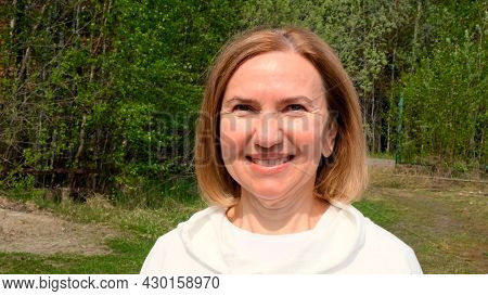 Pleased Beautiful Mature Woman Face. Mid Adult Lady Smiling Outdoors. Portrait Of Female Age 55-60 R