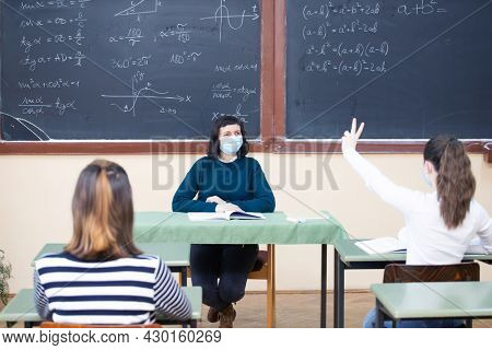 Teacher and her students wearing protective face mask in the classroom. Social distanting and classroom safety during coronavirus epidemic