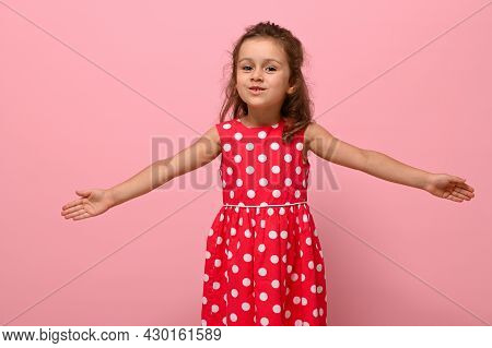 Smiling Happy Little Charming Girl With Outstretched Hands In A Pink Dress With Polka Dots, Looking