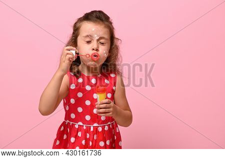 Portrait Of Cheerful Beautiful Baby Girl Blowing Soap Bubbles, Isolated Over Pink Background With Co